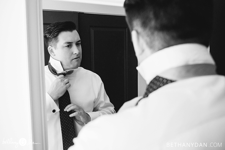 The groom making sure his tie is on right