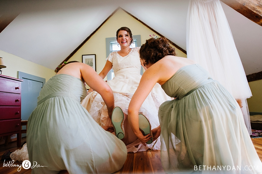 The bridesmaids help the bride get her shoes on