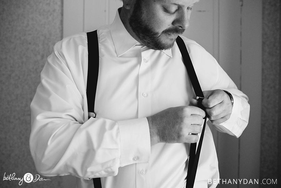 The groom adjusts his suspenders