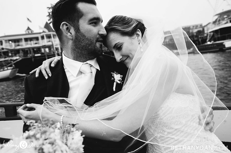 Bride and groom snuggle on boat